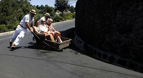 Carreiros push tourists in a sledge in Monte